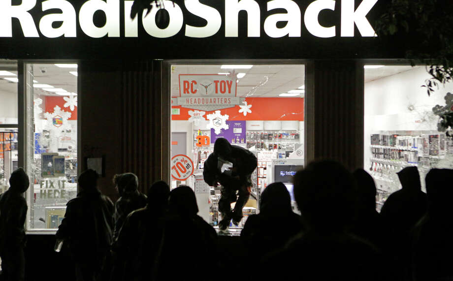 A looter leaps out of a Radio Shack on Shattuck Avenue in Berkeley after protests against police killings of unarmed black men in Missouri and New York spiraled into vandalism. Photo: Terray Sylvester / The Chronicle / ONLINE_YES