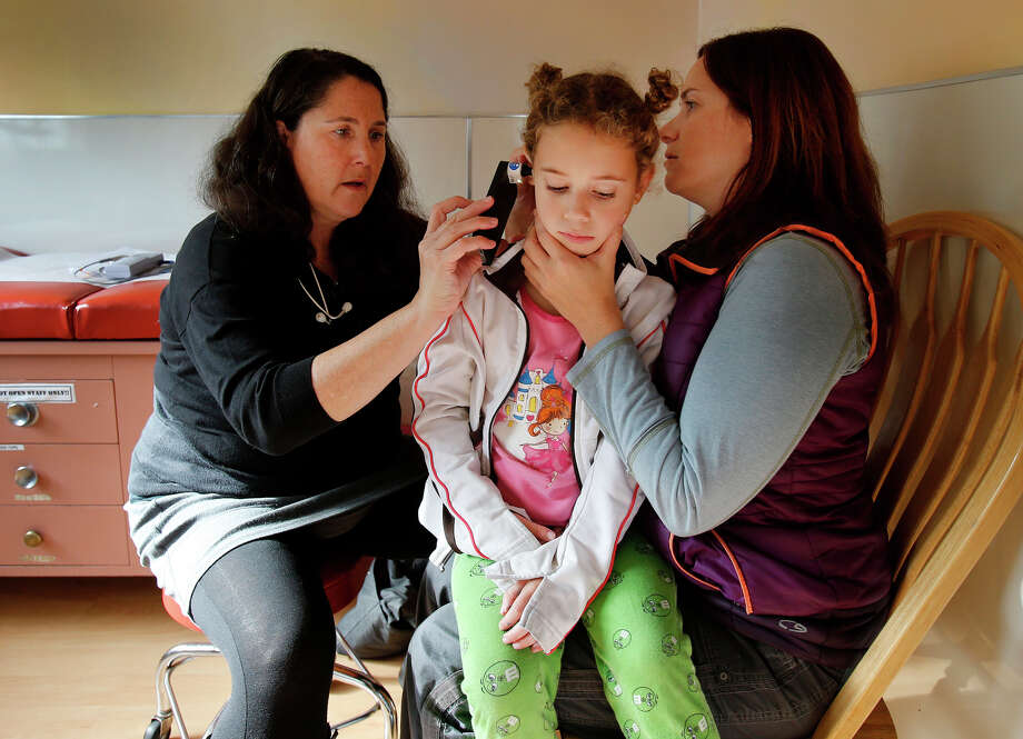 Izzy Cohen sits in her mother Jessica's lap as Dr. Jessica Kaplan examines her ears with a device made by San Francisco startup Cellscope, which attaches to a smartphone and enables high-resolution filming of the inside of the ear. Photo: Brant Ward / The Chronicle / ONLINE_YES