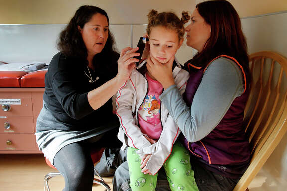Izzy Cohen sits in her mother Jessica's lap as Dr. Jessica Kaplan examines her ears with a device made by San Francisco startup Cellscope, which attaches to a smartphone and enables high-resolution filming of the inside of the ear.