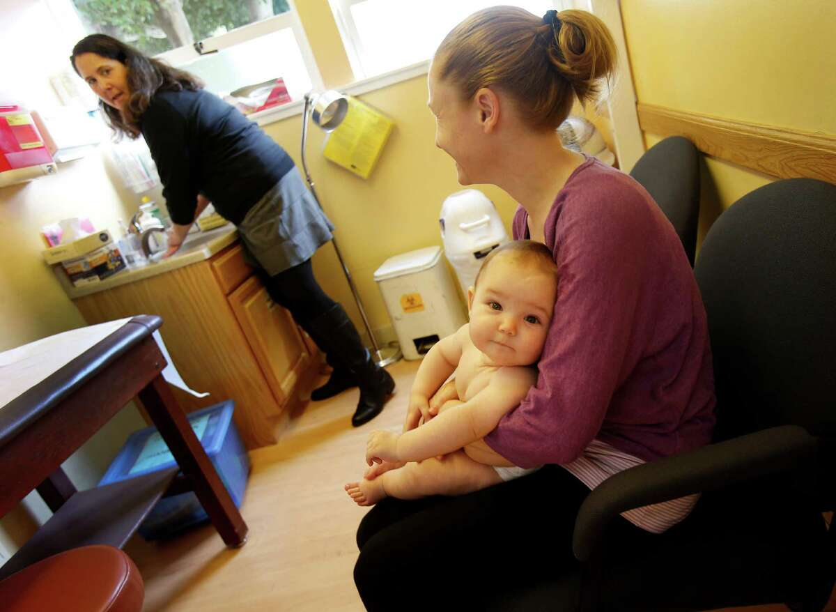 Six-month-old Adelise Fry is held by her mother Lyndsey as they wait for an examination by Dr. Jessica Kaplan (left) Noe Valley Pediatrics. Kaplan uses a device called the Oto by San Francisco startup which attaches to a smartphone to film the inside of the ear.