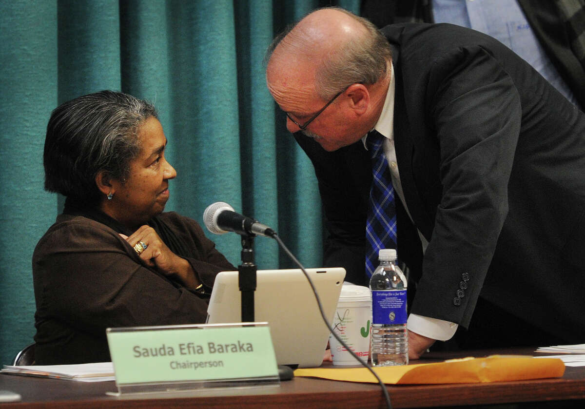 Newly elected Bridgeport Board of Education Chair David Hennessey, right, approaches outgoing Chair Sauda Baraka as members mingle following the board's election meeting at the Aquaculture School in Bridgeport, Conn. on Monday, December 8, 2014.