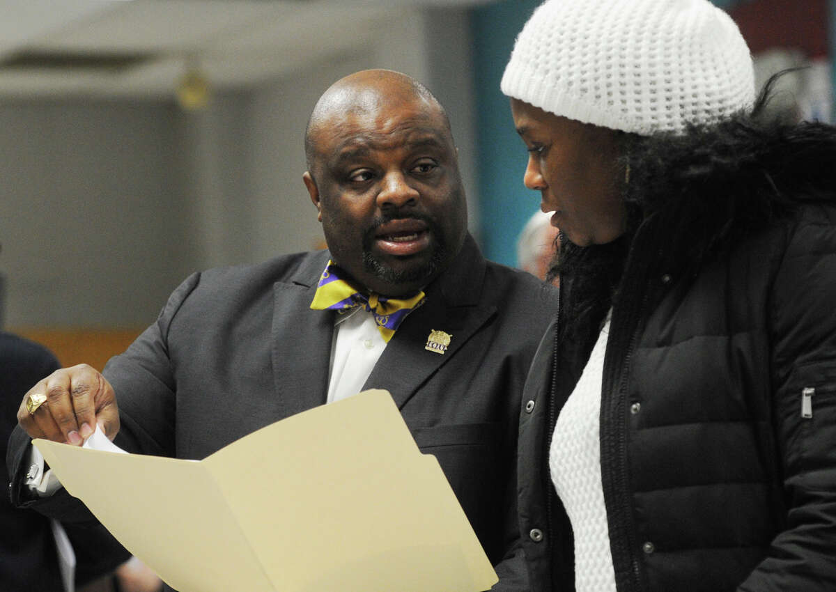 Bridgeport Board of Education member Kenneth Moales, Jr., left, talks with new board member Kadisha Coates following the board's election meeting at the Aquaculture School in Bridgeport, Conn. on Monday, December 8, 2014.