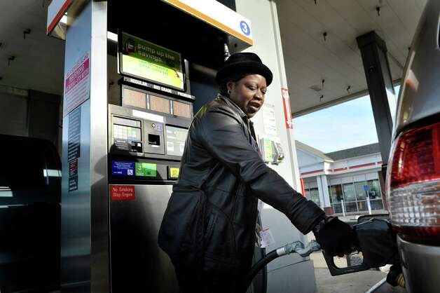 Gladys Robinson of Schenectady fills her car up with gas at the Cumberland Farms on Monday, Dec. 8, 2014, in Glenmont, N.Y.  (Paul Buckowski / Times Union) Photo: Paul Buckowski / 00029776A