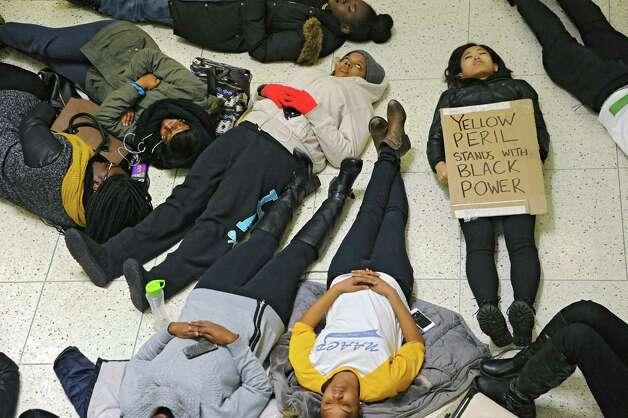 "The National Association For the Advancement of Colored People host a ""die-in"" to honor the lives of Eric Garner and Michael Brown in the campus center at the University of Albany on Monday, Dec. 8, 2014 in Albany, N.Y. The students participating in the protest laid down on the floor for 11 minutes which was the time it took Eric Garner to die when police put him in a chokehold. Senior student Juliet Shen of Phoenex, AZ holds a sign saying ""yellow peril stands with black power."" Yellow peril was a color metaphor for race in the 1960's associated with asians. (Lori Van Buren / Times Union) Photo: Lori Van Buren / 00029772A"