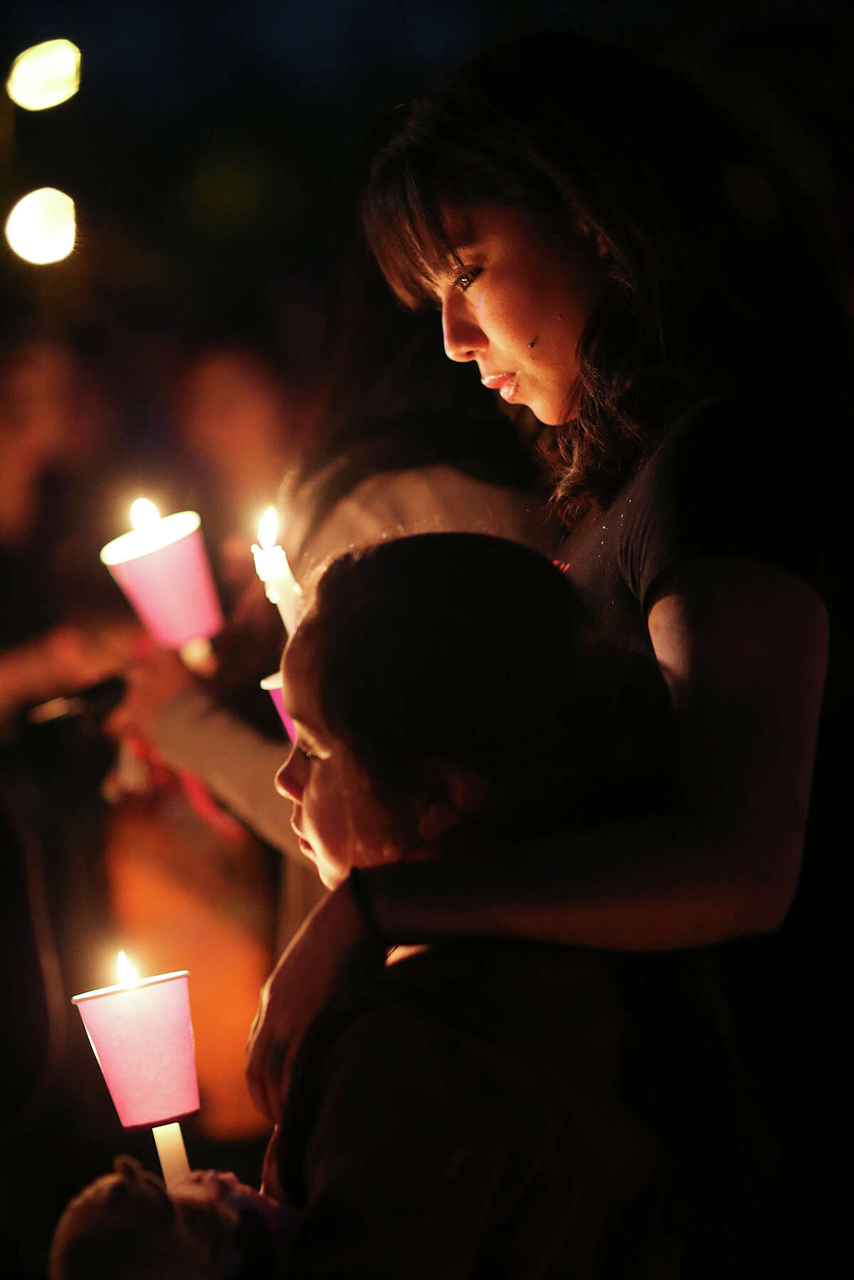 Angelina Vasquez, 8, is hugged by her aunt, Lorrina Robinson, 24, during a vigil for Vazquez' mother, Darlene Jessica Vasquez, 34, and Jenaro Covarrubias, 33, at 2302 Delgado, Monday, Dec. 8, 2014. The vigil was held at 2302 Delgado Street where the pair was murdered Sunday. The suspected shooter, Christopher Bernard Doss, 41, was killed by a member of the Lone Star Fugitive Task at a hotel on the 500 block of Roosevelt Avenue earlier in the day. During the incident, the suspect shot at the young girl but the bullet grazed her hand.