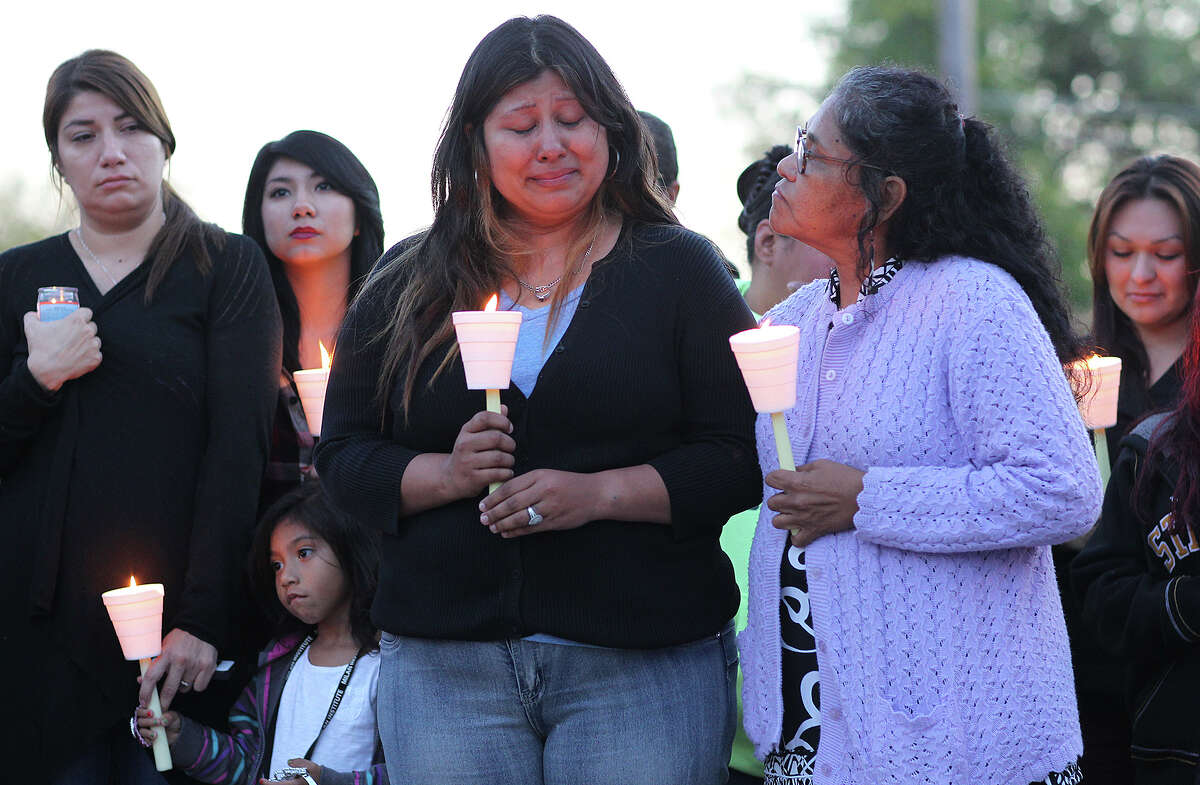 Ruby Hernandez, 30, center, reacts during a vigil for her brother, Jenaro Covarrubias, 33, and Darlene Jessica Vasquez, 34, Monday, Dec. 8, 2014. The vigil was held at 2302 Delgado Street where the pair was murdered Sunday. The suspected shooter, Christopher Bernard Doss, 41, was killed by a member of the Lone Star Fugitive Task at a hotel on the 500 block of Roosevelt Avenue earlier in the day. With her is her aunt, Yolanda Becerra.