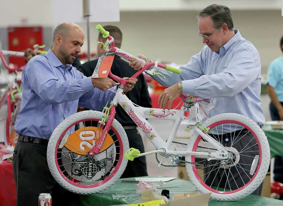 Team members with Freeman Houston assembles a bike at George R Brown Convention Center. Twenty seven team participate in the Hotel and Lodging Association of Greater Houston 15th Annual Bike Building Competition on Monday December 8, 2014 at the George R. Brown Convention Center in Houston, TX. Houston First Corporation was the first team to assemble two bikes and make two Christmas cards. Photo: Thomas B. Shea, For The Chronicle / © 2014 Thomas B. Shea