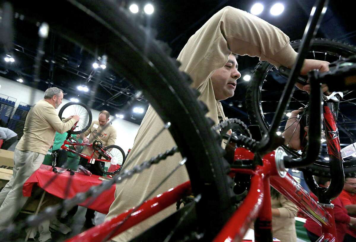 Team members from The Magnolia Hotel assemble a Huffy bicycle. Twenty seven team participate in the Hotel and Lodging Association of Greater Houston 15th Annual Bike Building Competition on Monday December 8, 2014 at the George R. Brown Convention Center in Houston, TX.