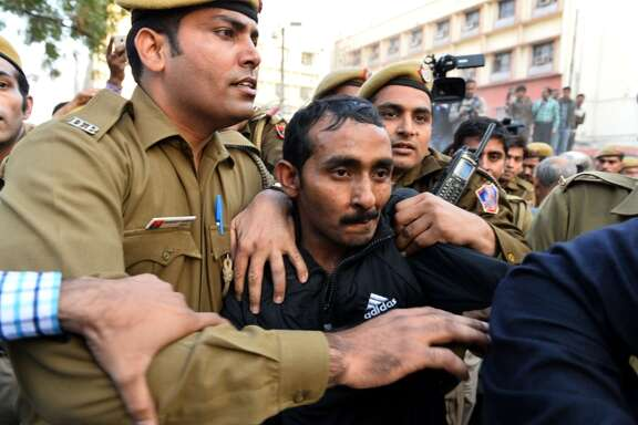 Police escort Shiv Kumar Yadav, who is accused of rape, after his court appearance in New Delhi.