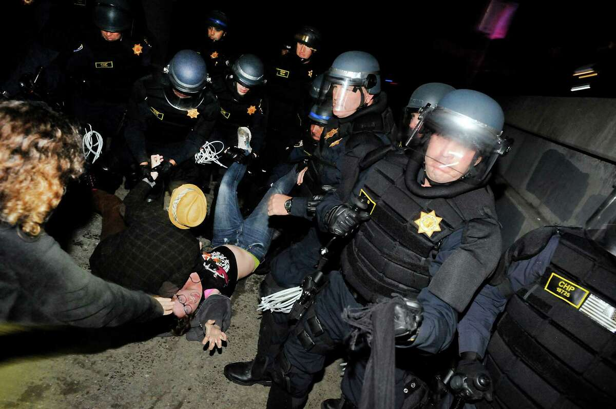 Police officers arrest protestors that sat down after being told to disperse from a bicycle path next to Highway 80 during a demonstration and march against grand jury decisions in Ferguson and New York, in Berkeley, CA, on Monday, December 8, 2014.