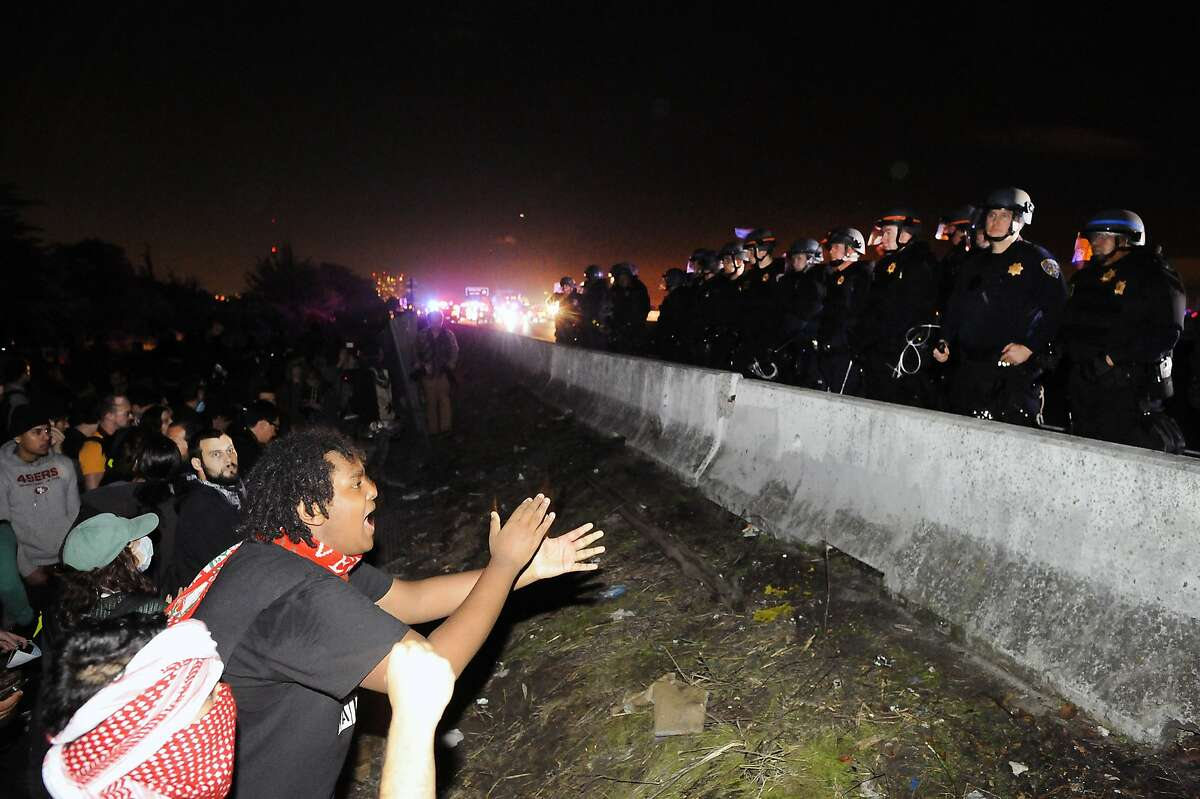 A line of police officers stands next to a divider after pushing back protestors that were blocking Highway 80 during a demonstration and march against grand jury decisions in Ferguson and New York, in Berkeley, CA, on Monday, December 8, 2014.