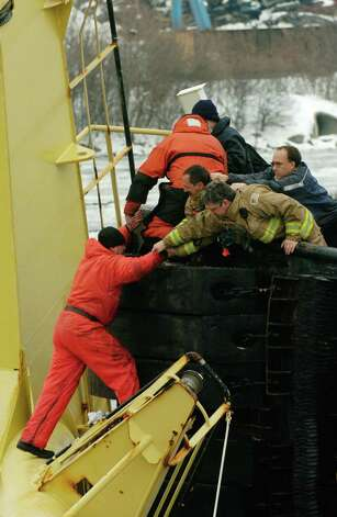 Times Union Staff Photo by Skip Dickstein    Rescue operations are in full swing after a ship overturned in the Port of Albany, New York December 9, 2003.  The accident occured when loading two GE turbines on to the Dutch Registry ship with a Russian crew of 18.  Three members of the crew are still missing.  Here a crew member is pulled from his shaky perch on the front mast of the overturned ship Stellamare. ORG XMIT: MER2013120907271614 ORG XMIT: MER2013120907320341 Photo: SKIP DICKSTEIN / ALBANY TIMES UNION