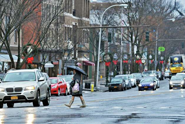 Pedestrians and motorists endure icy rain along Broadway Tuesday Dec. 9, 2014, in Saratoga Springs, NY.  (John Carl D'Annibale / Times Union) Photo: John Carl D'Annibale / 00029785A