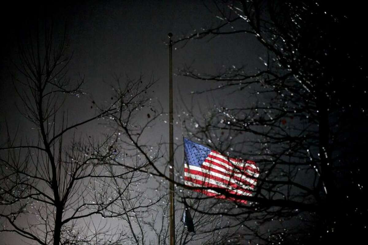 A U.S. flag flies at half staff outside the Newtown High School before President Barack Obama is scheduled to attend a memorial for the victims of the Sandy Hook Elementary School shooting, Sunday, Dec. 16, 2012, in Newtown, Conn. A gunman walked into Sandy Hook Elementary School in Newtown Friday and opened fire, killing 26 people, including 20 children.