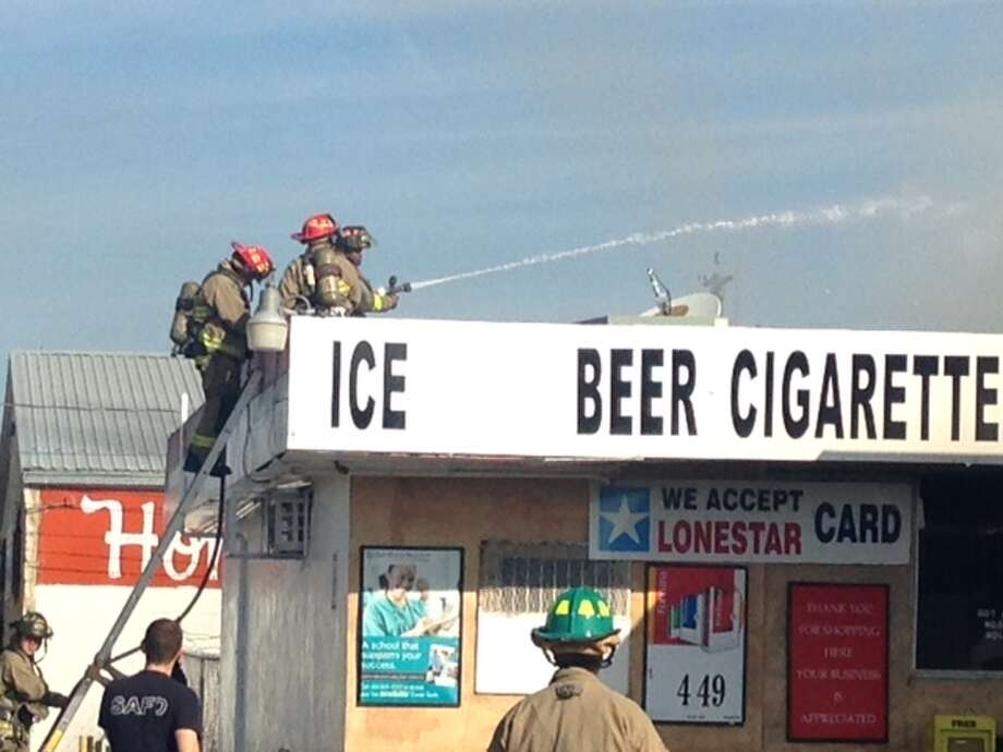 Firefighters are working to extinguish a blaze at the MLK Food Mart on the East Side. Photo: Mark D. Wilson/San Antonio Express-News