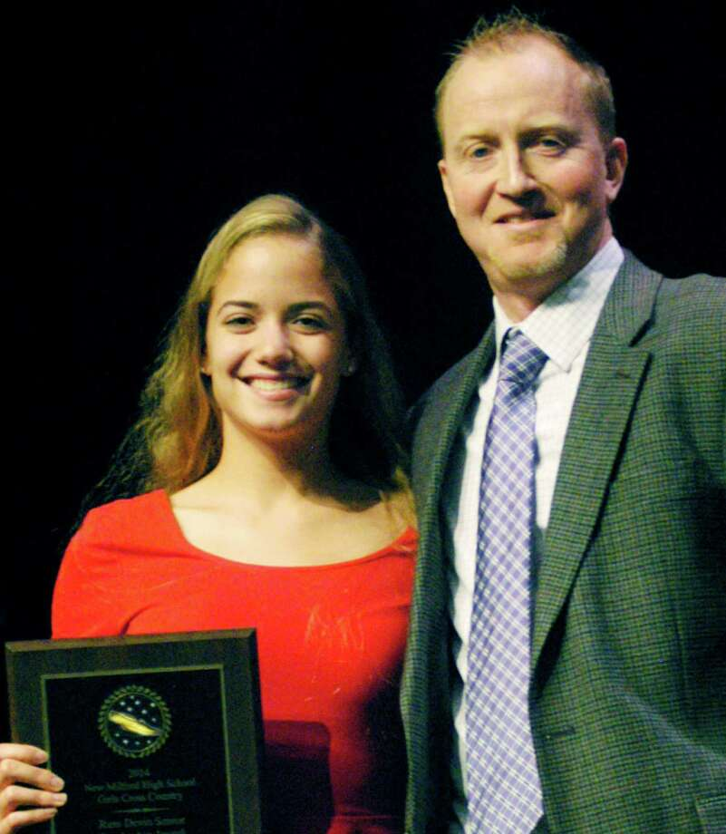 Nicole McCarthy is presented her team's Russell Devin Award by Green Wave girls' cross country coach Giles Vaughan during New Milford High School's annual fall sports awards ceremony, Dec. 1, 2014. The award is given each year to a standout senior in memory of Devin, the legendary Green Wave cross country and track coach. Photo: Norm Cummings / The News-Times