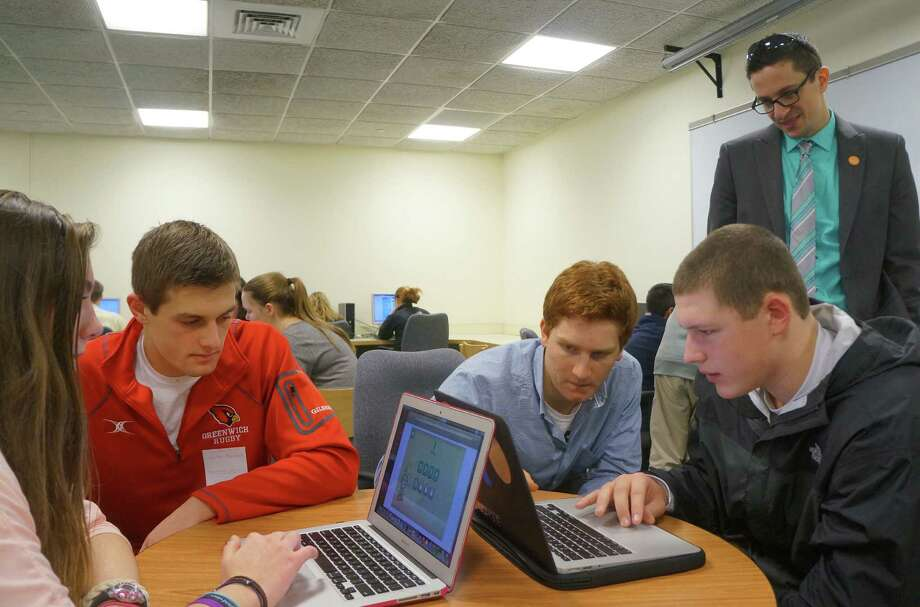 Greenwich High School students do computer programming during the 'Hour of Code' day. From left, are: junior Lisa Lewis, junior Luke Bienstock, senior Griffin Golden, teacher Matt Meyers and junior Kevin Woodring. Tuesday, Dec.9, 2014, Greenwich, Conn. Photo: Paul Schott / Greenwich Time