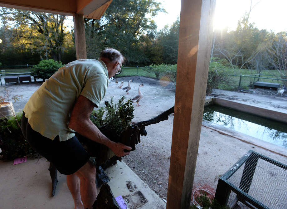 Ralph Beard lifts one of his handmade driftwood troughs on his back porch Monday afternoon. Photo taken Monday 11/24/14 Jake Daniels/The Enterprise Photo: Jake Daniels / ©2014 The Beaumont Enterprise/Jake Daniels