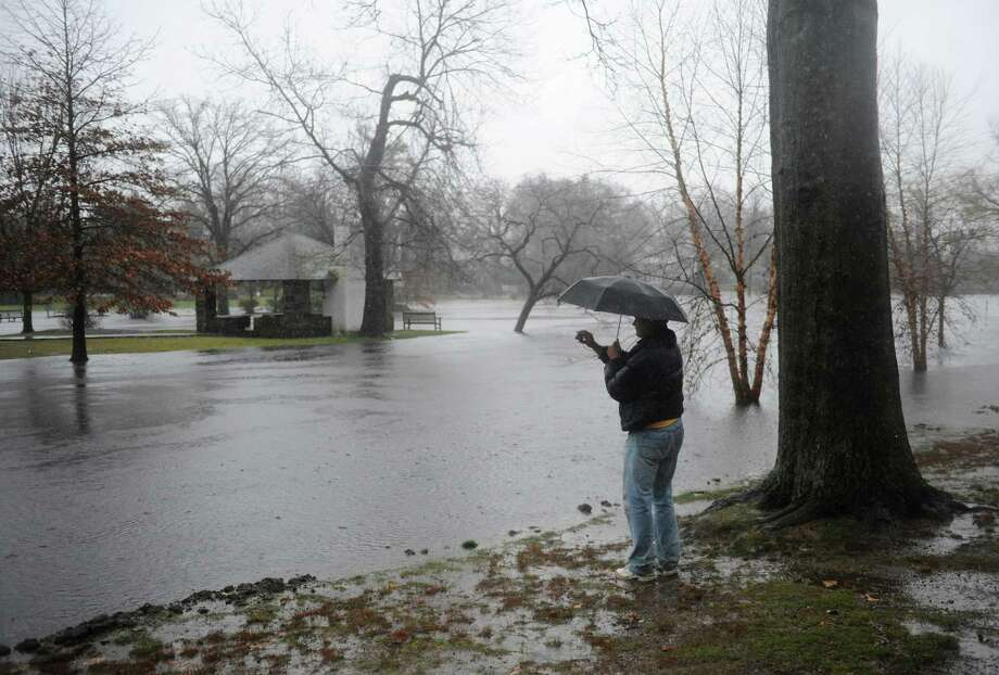 Greenwich resident John Hayes takes a photo of the flooded Binney Park in Old Greenwich, Conn. Tuesday, Dec. 9, 2014.  Rainfall began early Tuesday morning and is expected to continue into Wednesday. Photo: Tyler Sizemore / Greenwich Time