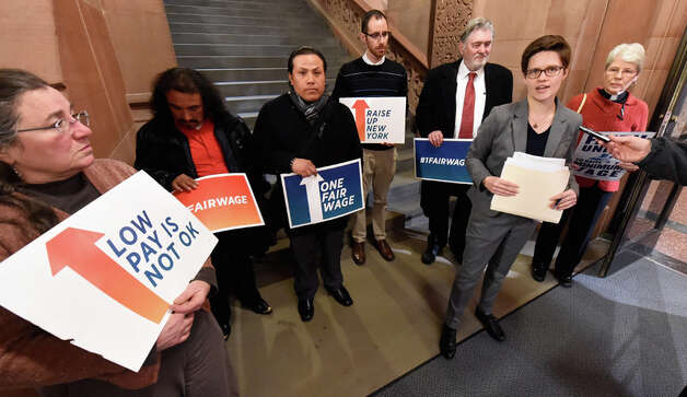 Emily McNeil, Labor Religion Coalition of NYS, is joined by other workers' advocates in calling for Gov. Cuomo to eliminate the sub-minimum wage for New York's tipped workers during a press briefing in the State Capital Tuesday morning, Dec. 9, 2014, in Albany, N.Y.  (Skip Dickstein/Times Union) Photo: SKIP DICKSTEIN, ALBANY TIMES UNION / 00029784A