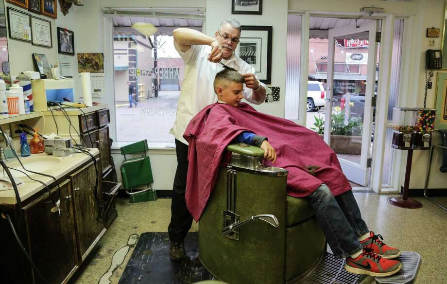 Leon Apostolo, barber and proprietor of the old-school Shepard's Barbershop, in Conroe, in action in December 2014. Photo: Billy Smith II, Chronicle / © 2014 Houston Chronicle