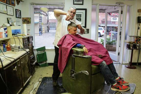 Leon Apostolo barber and proprietor of Shepard's Barbershop cuts the hair of ten year-old Kyle Isbell Tuesday December 2, 2014 at Shepard's  Barbershop in downtown Conroe, Tx. Shepard's Barbershop is the oldest continuous operating barbershop in Montgomery County. The building owned by Bob Shepard was built in 1914 and became a barbershop in 1922. Leon Apostolo who has been working  at the Shepard's since 1978 currently operates Shepard's Barbershop.