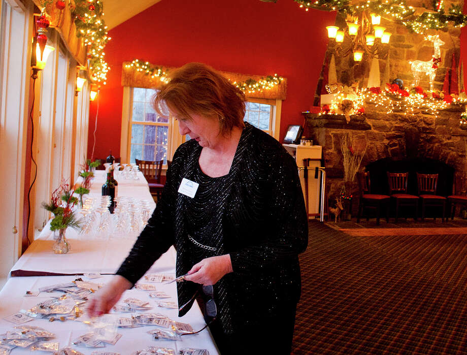 Executive Vice President Barbara Seiter organizes nametags in preparation for the Stamford Chamber of Commerce's annual holiday party at Zody's 19th Hole in Stamford, Conn., on Tuesday, December 9, 2014. Photo: Lindsay Perry / Stamford Advocate
