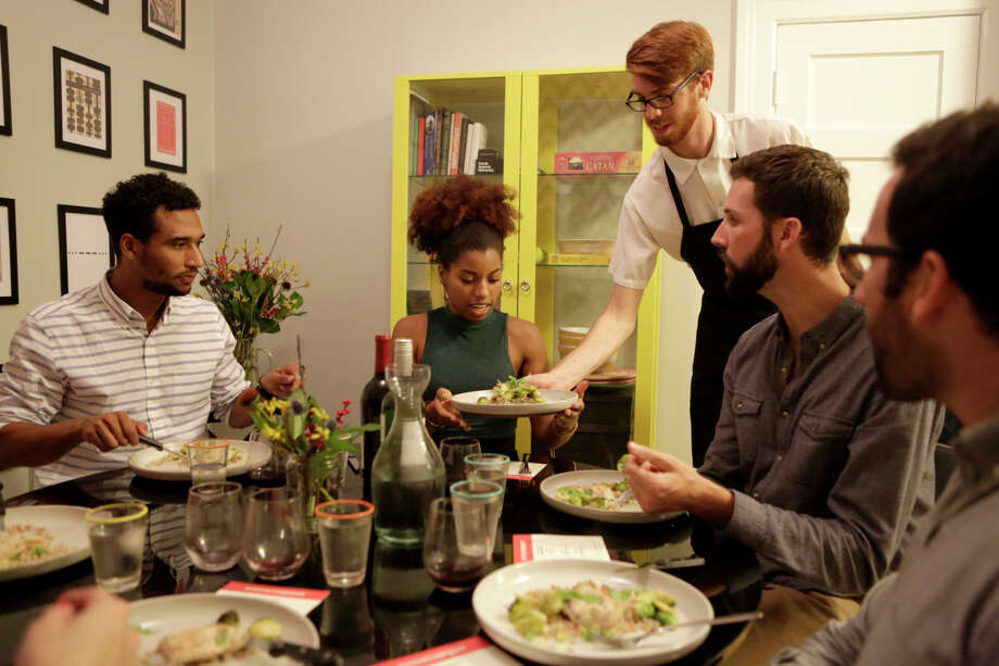 Colin Mealey serves plates of chicken at a dinner party in the home of Ian Ferguson, one of Kitchit's founders. Photo: Terray Sylvester / The Chronicle / ONLINE_YES