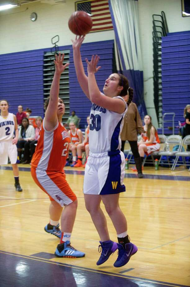 Westhill's Elizabeth Grasso puts up a shot as Danbury's Kayla Handberry defends during Friday's girls basketball game at Westhill High School in Stamford, Conn., on January 10, 2014. Photo: Lindsay Perry / Stamford Advocate