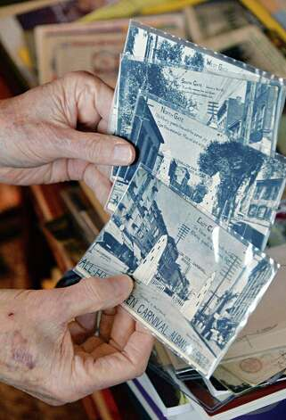 Robert Drew, a deltiologist or postcard collector, holds a set of postcards from an Albany Halloween carnival from 1905, Friday Dec. 5, 2014, in Albany, NY. (John Carl D'Annibale / Times Union) Photo: John Carl D'Annibale / 00029763A
