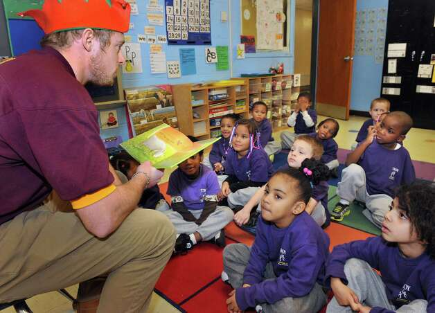 Joachim Thrane reads to School 2 students as he and fellow RPI fraternity members of Pi Kappa Alpha continue their long tradition of delivering Christmas toys to School 2 students Tuesday Dec. 9, 2014, in Troy, NY.  (John Carl D'Annibale / Times Union) Photo: John Carl D'Annibale / 00029768A