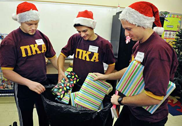 RPI fraternity members, from left, Michael Piekarz, Chris Rea, and Peter Quinan, of Pi Kappa Alpha unpack Christmas presents for School 2 students Tuesday Dec. 9, 2014, in Troy, NY.  (John Carl D'Annibale / Times Union) Photo: John Carl D'Annibale / 00029768A