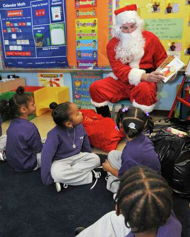 Dressed as Santa, Keagan Devereaux, top, reads to School 2 students as he and fellow RPI fraternity members of Pi Kappa Alpha continue their long tradition of delivering Christmas toys to School 2 students Tuesday afternoon, Dec. 9, 2014, in Troy, N.Y.  (John Carl D'Annibale / Times Union) Photo: John Carl D'Annibale / 00029768A