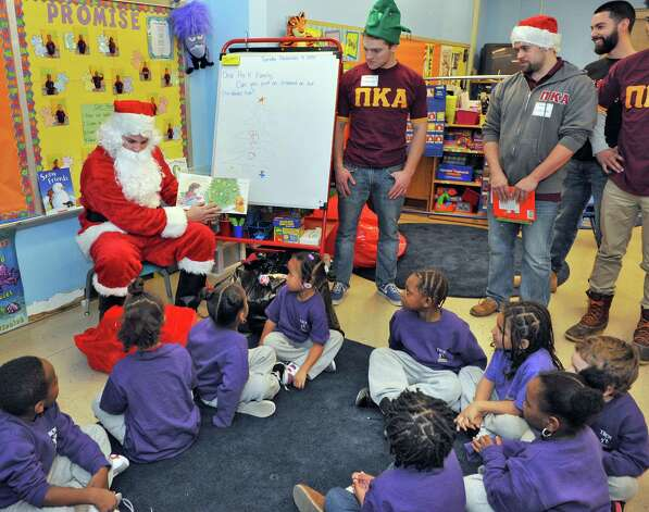 Dressed as Santa, Keagan Devereaux, left, reads to School 2 students as he and fellow RPI fraternity members of Pi Kappa Alpha continue their long tradition of delivering Christmas toys to School 2 students Tuesday, Dec. 9, 2014, in Troy, N.Y.  (John Carl D'Annibale / Times Union) Photo: John Carl D'Annibale / 00029768A