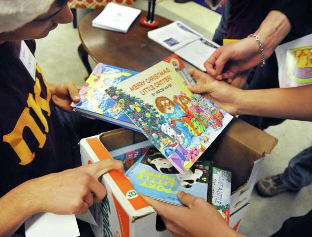 RPI fraternity members of Pi Kappa Alpha choose books to read to students as they continue their long tradition of delivering Christmas toys to School 2 students Tuesday Dec. 9, 2014, in Troy, NY.  (John Carl D'Annibale / Times Union) Photo: John Carl D'Annibale / 00029768A