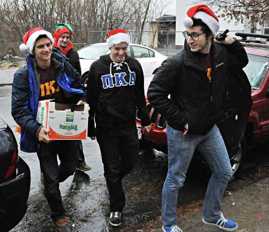 RPI fraternity members, from left, Chris Rea, Lucas Tucker, Peter Quinan and Gavin Norvitsky, of Pi Kappa Alpha carry Christmas presents and books for School 2 students Tuesday Dec. 9, 2014, in Troy, NY.  (John Carl D'Annibale / Times Union) Photo: John Carl D'Annibale / 00029768A