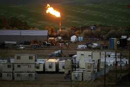 FILE - In this June 9, 2014 file photo, the burn off flame of natural gas lights up the night sky in Williston, N.D. North America.  (AP Photo/Charles Rex Arbogast, File)