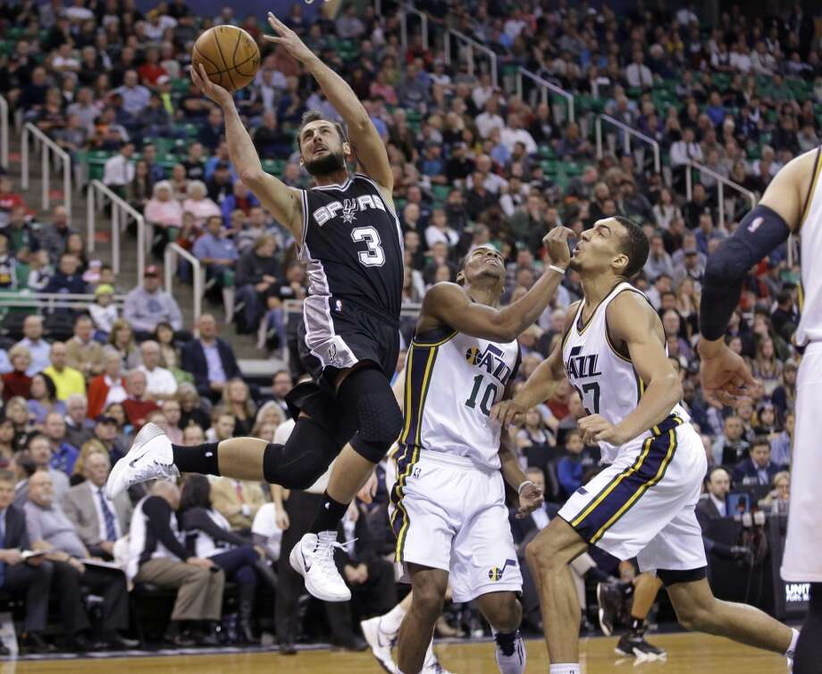 San Antonio Spurs' Marco Belinelli (3) goes to the basket as Utah Jazz's Alec Burks (10) and Rudy Gobert (27) defend in the second quarter during an NBA basketball game Tuesday, Dec. 9, 2014, in Salt Lake City.  (AP Photo/Rick Bowmer) Photo: AP