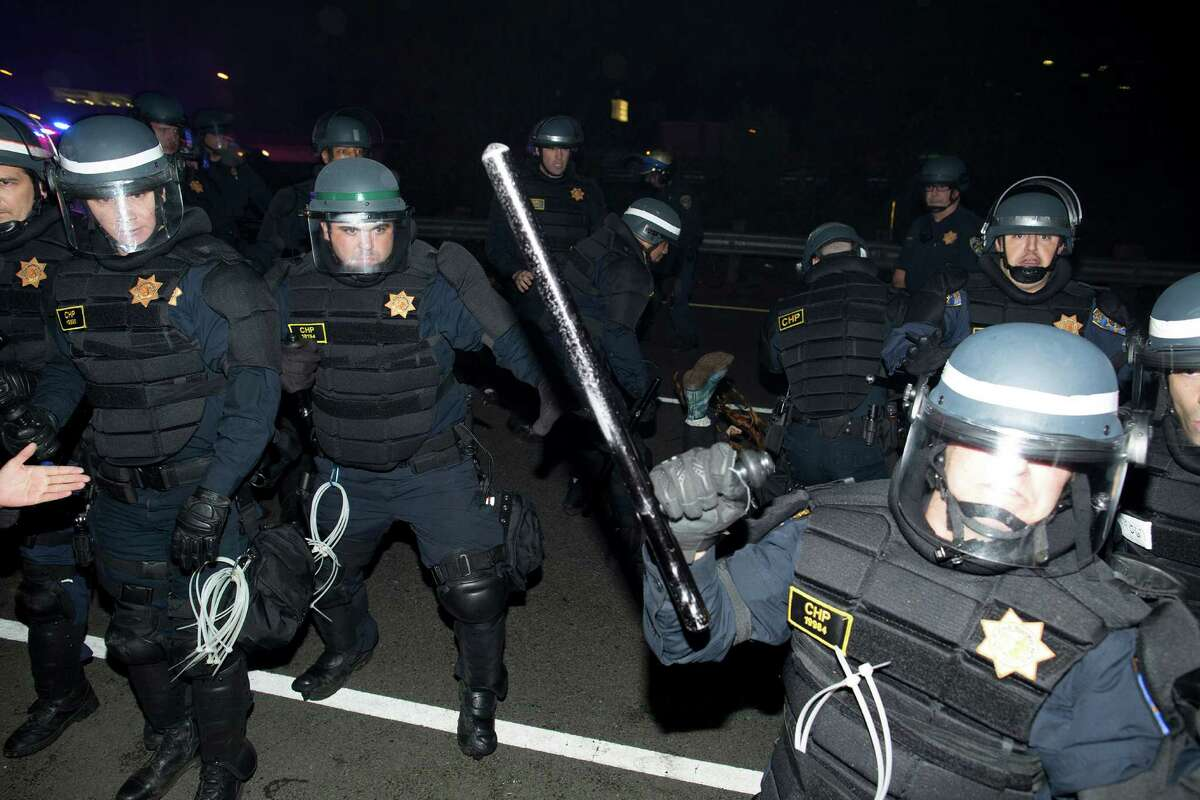 Police push back protesters in Oakland as they demonstrate against grand jury decisions in Ferguson and New York, in Berkeley, Calif., on Tuesday, December 9, 2014.