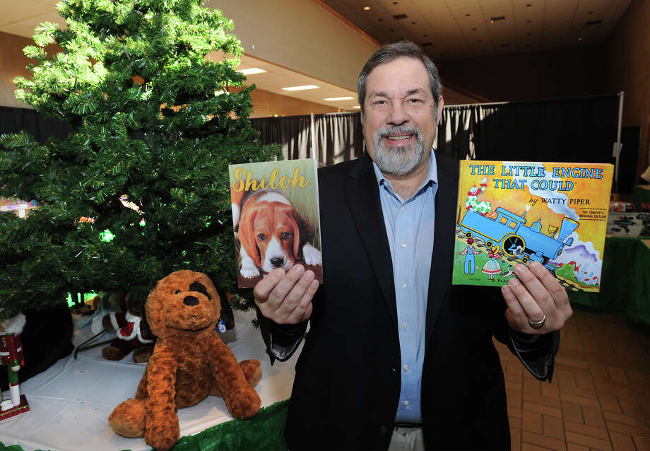 """Mike Fuljenz holds up """"Shiloh"""" and """"The Little Engine that Could"""" during the Empty Stocking toy distribution event at the Civic Center on Tuesday. Fuljenz donated $6,000 worth of books to the EJ fund.  Photo taken Tuesday, December 9, 2014  Guiseppe Barranco/The Enterprise Photo: Guiseppe Barranco, Photo Editor"""