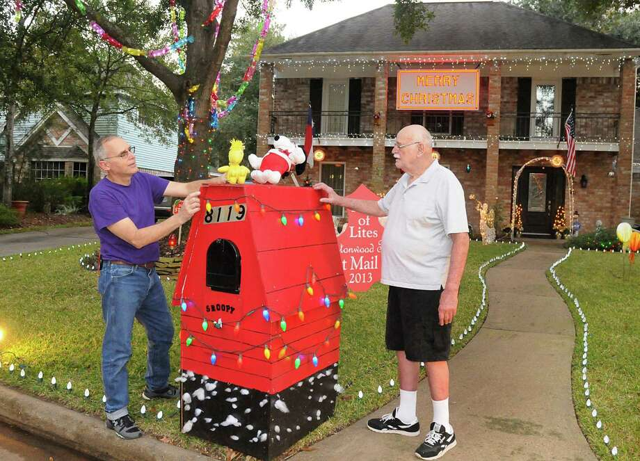 steven jackson and his father sam add lights to snoppys dog house at jacksons - Prestonwood Forest Christmas Lights