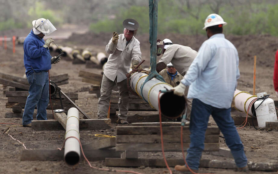 Welding crews lay pipe to carry oil from a field near Karnes City in 2011. Activity has subsided along with oil prices. Photo: JOHN DAVENPORT, SAN ANTONIO EXPRESS-NEWS