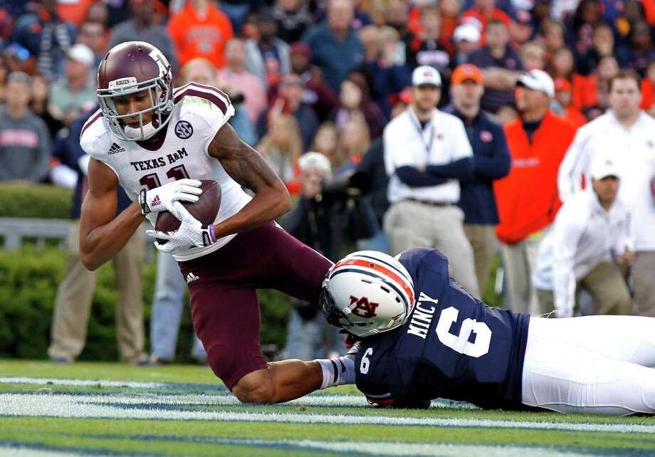 Texas A&M wide receiver Josh Reynolds (11) catches a pass for a touchdown as Auburn defensive back Jonathon Mincy (6) tackles him during the first half of an NCAA college football game on Saturday, Nov. 8, 2014, in Auburn, Ala. (AP Photo/Butch Dill) Photo: Butch Dill, FRE / Associated Press / FR111446 AP