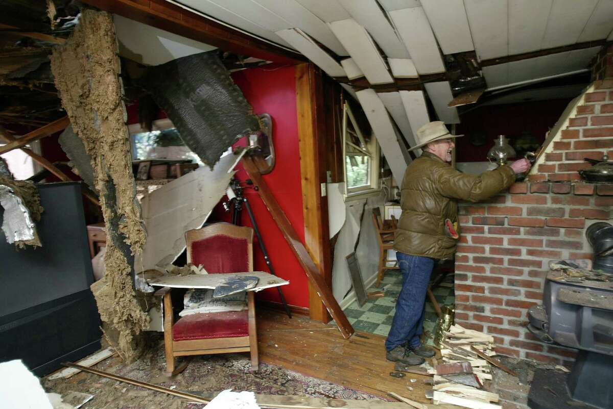 Steve Owen, a 63-year-old retiree, salvages bits of his antique collection from his home on December 15, 2006. The house was sliced in half by two fallen Douglas fir trees that blew over in the night. Owen spent the remainder of the night sleeping in his car inside his garage.