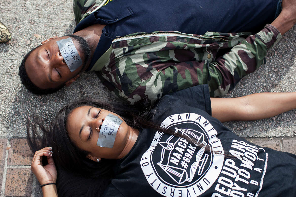 """UTSA senior Ashely Andrews and junior Chad Davis lay Wednesday Dec. 10, 2014 during a """"Die-in"""" in honor of Michael Brown and Eric Garner, where they laid for 15 and half minutes at Sombrilla Plaza. The event was sponsored by the UTSA NAACP chapter in an effort to shed light on police brutality and injustice, with about 80 people participating."""