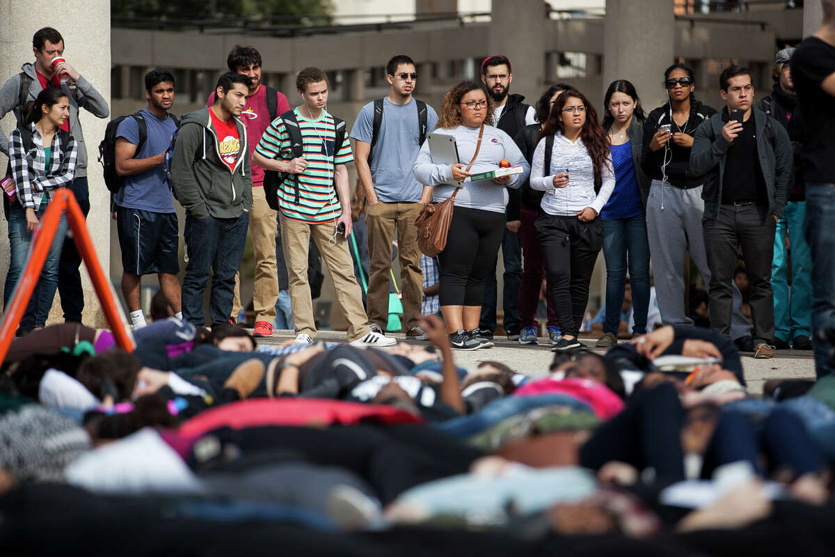 """A crowd watches as about eighty UTSA students gathered at Sombrilla Plaza Wednesday Dec. 10, 2014 for a """"Die-in"""" in honor of Michael Brown and Eric Garner, where they laid for 15 and half minutes. The event was sponsored by the UTSA NAACP chapter in an effort to shed light on police brutality and injustice."""