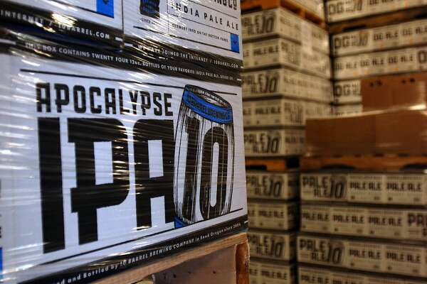 In this Nov. 18, 2014 photo, cases of Apocalypse IPA from 10 Barrel Brewing Co. await shipment in Bend, Ore. As it grew from a struggling timber town to an outdoor recreation destination, Bend, Ore., has seen an explosion of breweries, making it one of the top beer towns in the country. When 10 Barrel announced it was being bought by the world's biggest brewer, Anheuser-Busch Inbev, many local beer lovers felt betrayed. (AP Photo/Jeff Barnard)