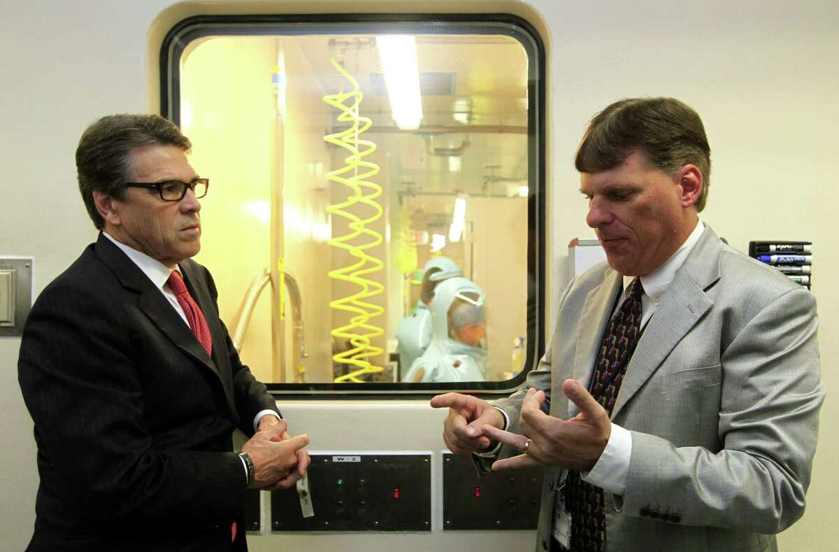 Tom Geisbert, right, a professor of microbiology and immunology at the University of Texas Medical Branch, with then-Gov. Rick Perry in 2014. Geisbert is theprimary investigator on a study of a new medication that could better treat full-blown cases of ebola.