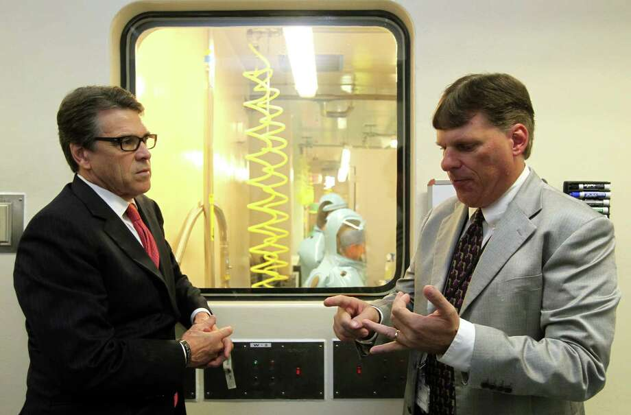 Tom Geisbert, right, a professor of microbiology and immunology at the University of Texas Medical Branch, with then-Gov. Rick Perry in 2014. Geisbert is the primary investigator on a study of a new medication that could better treat full-blown cases of ebola.  Photo: Jennifer Reynolds, Associated Press / Pool The Daily News