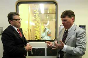 Tom Geisbert, right, a professor of Microbiology and Immunology at the University of Texas Medical Branch, explains to Texas Gov. Rick Perry the work researchers are conducting in a Bio Safety Level 4 lab in the Galveston National Laboratory on Tuesday, Oct. 7, 2014. Perry and other state officials toured the national laboratory a day after he created a Task Force on Infectious Disease Preparedness and Response. (AP Photo/The Daily News, Jennifer Reynolds, Pool)